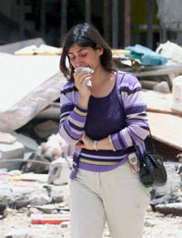 A women cries as she walks past a house destroyed by a terrorist attack in Saudi Arabia
