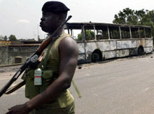 Soldier patrols Abidjan after rioters torched a bus in protest of the murder of two prominent opposition figures.