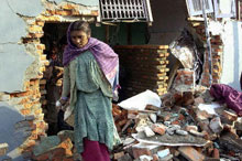 A Nepalese woman walks by a bombed-out children's hospice