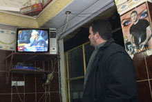 An Iraqi Kurd watches Al-Jazeera's live coverage of U.S. Secretary of State Colin Powell's address to the U.N. Security Council