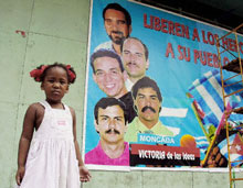 A Cuban girl stands by a mural depicting five men imprisoned in the United States as spies.