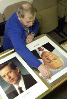 A Czech civil servant replaces the portraits of the Czech president
