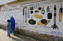 A Kabul woman and child walk past a mural depicting landmines to avoid.