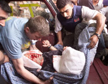 Journalists carry a wounded Reuters cameraman out of the Palestine Hotel in Baghdad