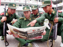 Chinese soldiers read about the war in Iraq