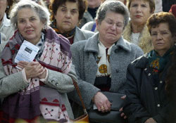 Women cry at a memorial at the Atocha train station in Madrid, April 11, 2004, one month after terrorists bombed the station.