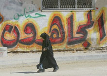 A Palestinian girl walks by Hamas graffiti in Gaza
