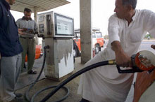 An Iraqi man fills his tank with gas