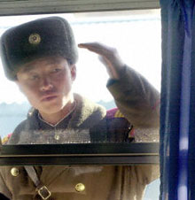 A North Korean soldier peers in at inspectors