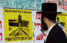 An Israeli man looks at a poster reading 'stop the road map to Auschwitz'