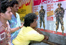 Sri Lankans read an army recruitment poster