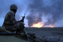 A British soldier watches oil fields burning in southern Iraq