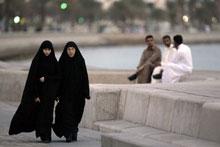 Qatari women stroll along the corniche in Doha