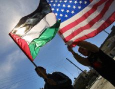 International peace activists hold up an American flag next to a Palestinian flag in Ramallah, Feb. 5, 2002