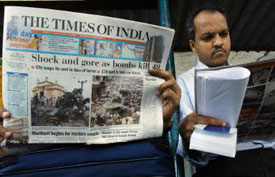 Indian commuters read about the Aug. 25 terrorist attacks in Mumbai