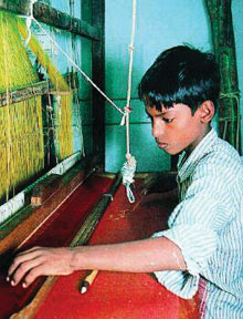 A boy works a silk loom in southern India
