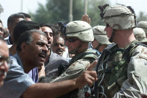 Jobless Iraqi soldiers yell at U.S. soldiers guarding the U.S. Office of Reconstruction and Humanitarian Affairs in Baghdad