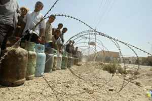 Iraqis wait in line to refill canisters of cooking gas