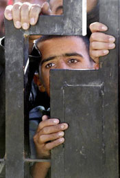 An Iraqi boy looks through the gates of a police station in Ouja, in northern Iraq