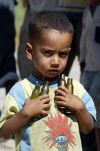 An Iraqi child carries spent shells