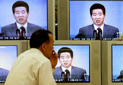 A man watches South Korean President Roh Moo-hyun confess that he doesn't feel up to his job on television, Oct. 10, 2003