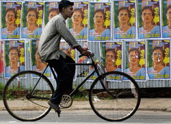 A Colombo man bicycles past defaced poster of Sri Lankan President Chandrika Bandaranaike Kumaratunga