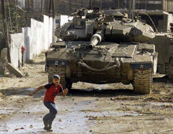 A Palestinian boy runs away from Israeli tanks in the West Bank town of Jenin