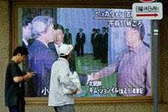 Tokyo residents walk bast a TV screen showing Koizumi shaking Kim Jong-Il's hand