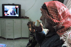 Palestinian man watches TV