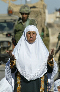 A Palestinian woman prays in front of an Israeli soldier at a West Bank checkpoint during Ramadan