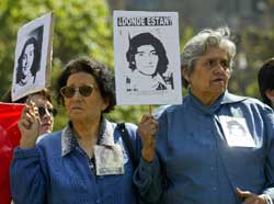 Chilean demonstrators holding pictures of relatives tortured and killed