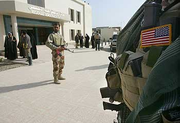 American and Iraqi soldiers stand guard in Hilla
