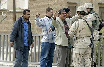 U.S. soldiers search Iraqis in central Baghdad