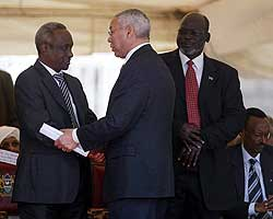 U.S. Secretary of State Colin Powell (center) congratulates Sudan's Vice President Ali Osman Taha
