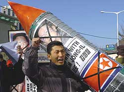 A South Korean activist holding a mock nuclear missile shouts slogans during an anti-North Korea rally