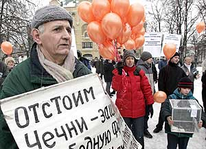"A man holds a poster that says ""Defend the freedom of Chechnya"""