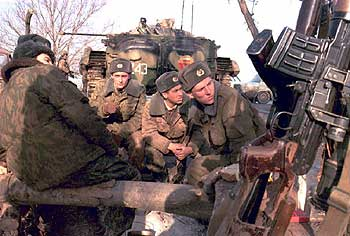 Russian troops sit around a fire with their machine guns