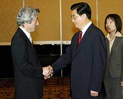 Japanese Prime Minister Junichiro Koizumi (left) greets Chinese President Hu Jintao