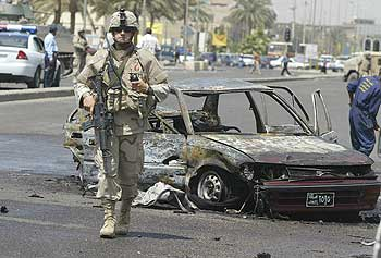 A U.S. soldider secures the site of a suicide car bomb explosion