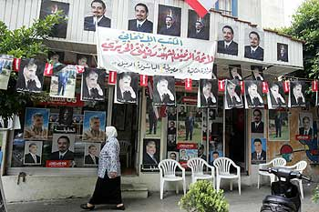 A Lebanese woman walks past election campaign posters of Saad Hariri