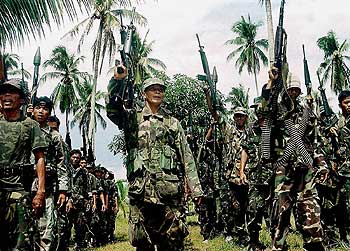 Members of the Moro Islamic Liberation Front parade during a press conference on the island of Mindanao