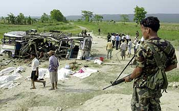 A Nepalese soldier stands guard at the wreckage of a passenger bus
