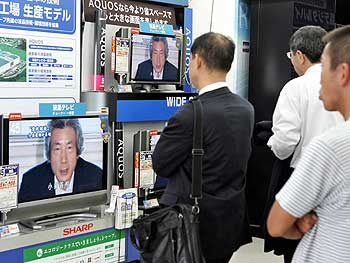 Japanese shoppers gaze at television news reporting that Koizumi will call a general election