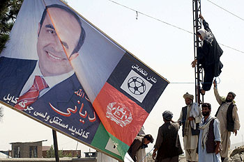 Afghan workers set up an electoral poster