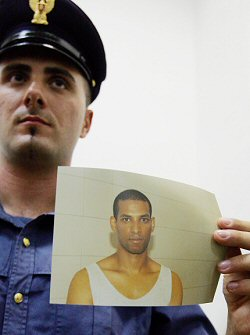 An Italian police officer shows the photo Hussain Osman
