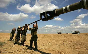 Israeli soldiers clean the cannon of 155mm mobile artillery