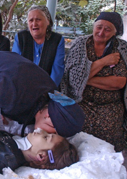A mother kisses her deceased child