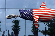 Floridians display their patriotism by hanging a shark, decorated in stars and stripes and eating a fish marked